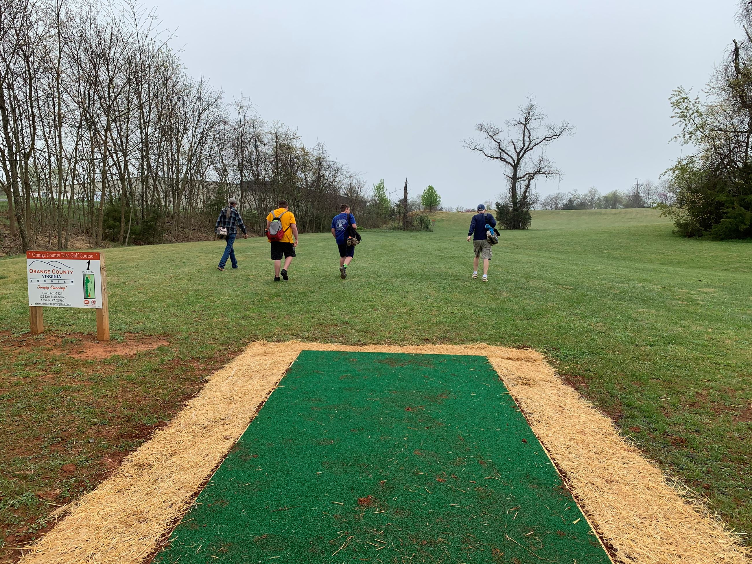 Players walk along hole number 1 at the Orange County Disc Golf Course.